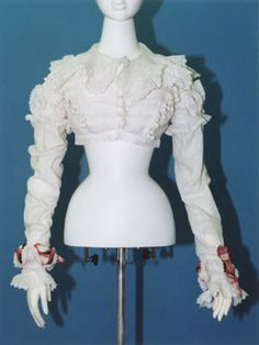 c. 1818, Spencer- white cotton lawn with hussar-style braid and pompoms, frills and small ball decorations all over.  KCI