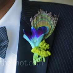 The groomsmen wore a single peacock feather and hypericum berries. The boutonniere was similar but also included a dendrobium petal.