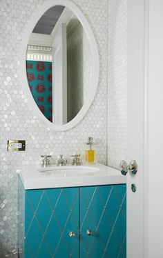 Amazing bathroom with Iridescent glass hex tile backsplash and turquoise blue bathroom vanity. Turquoise blue bathroom vanity with white quartz countertop and white oval mirror. Bathroom bi-fold doors with octagonal faceted door knob. Mirror Cabinets, Bathroom Wall Tile, Small Bathroom Decor, Bathroom Trends, Shower Backsplash, Amazing Bathrooms, Vanity Backsplash, Bathroom Wallpaper, Tile Bathroom