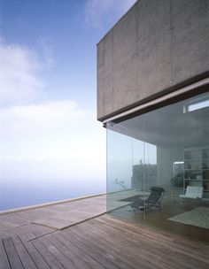 Monolithic concrete and glass house on a cliff edge by Corona + P. Amaral Architects