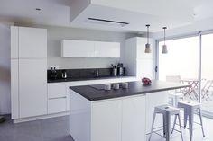 Agence Skéa Designer | www.skeadesigner.com | Cette cuisine blanche et grise se veut élégante et atemporelle. Le style vintage des tabourets tranche avec le contemporain de cette cuisine pour lui apporter plus de caractère. Deux suspensions en béton et bois donnent du charme à cet espace.