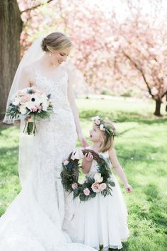 Bride and her adorable flower girl under a gorgeous Cherry Blossom tree: http://www.stylemepretty.com/little-black-book-blog/2016/08/22/traditional-spring-blush-wedding-cherry-blossoms/ Photography: Alea Lovely - http://www.alealovely.com/