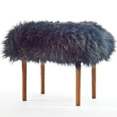 This long legged real sheepskin footstool is the Ceri in Coal Black. It's a luxury sheepskin footstool with a stylish turned and tapered dark oak coloured as always the cover it removable, handmade in beautiful North Wales.