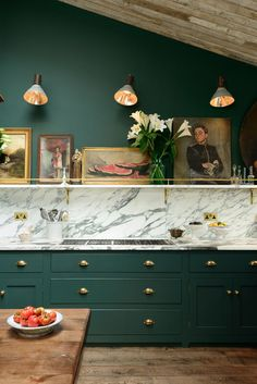 Gorgeous racing green cabinets, dramatic marble backsplash and bold brass hardware creates a timeless yet modern look in this chic English kitchen.