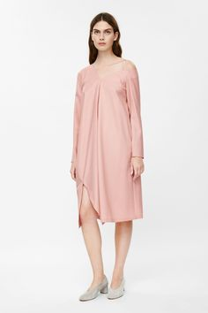 Designed with asymmetrical shapes, this dress is made from lightweight wool with a partial silky lining. A loose, oversized, fit, it has a grosgrain band across one shoulder, long sleeves, in-seam pockets and a front split hemline.