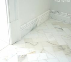 """Bathroom: all Calacatta marble, which is not as gray or muddy as Carrara. Carrara is popular; but the morning light of this room wanted warmer, clearer tones. Shower stall: 12x12 wall tiles and mosaic shower floor. Mosaic tiles work great in shower floors. Arranged on flexible sheets, the mini pieces conform well to the pitch of a shower floor. Plus the texture reduces slipping. Herringbone 3x6"""" floor tiles, custom 1-piece thresholds, carved baseboard tiles, Notice grout lines are barely…"""