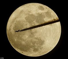 """An airplane flying in front of the May 5th 2012 """"Super Moon"""""""