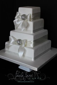 Square cakes with ivory satin ribbon and heirloom brooch