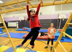 Cayra Arellano, a first-grader,  swings through the course as  PE teacher, Beth Buchanan, watches. Students at Ryan Elementary School in Lafayette are training on an obstacle course to become ninjas. For more photos, go to www.dailycamera.com. Cliff Grassmick  Staff Photographer  February 9, 2016