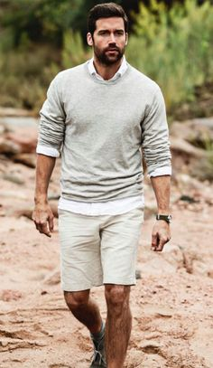 Very put together look in neutral shorts, sweater, and button up shirt.