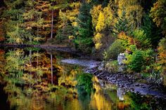 A couple stops to take a picture of the autumn colors at Loch Faskally on October 24, 2014 in Pitlochry, Scotland.