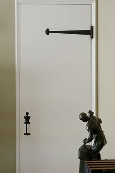 Original iron strap-hinge and thumb-latch hardware stands out on a simple plank door.