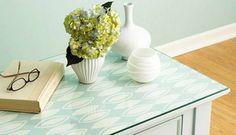 Com papel colorido, uma mesa qualquer no canto da sala ganha vida. Vale usar um tampo de vidro para o revestimento durar mais Foto: Homedit...