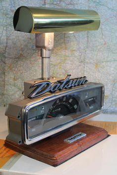 The Datsun Lamp is a unique light made from vintage Datsun parts. The base is made from a 1970 Datsun pickup dash panel and is attached to a solid wood plaque. It turns on with a heavy duty toggle switch on the back of the lamp. It includes a fish tank style light bulb. It measures 13 long, 7 wide, by 13 high. Perfect for the vintage Japanese car enthusiast, or anyone who likes groovy cars.