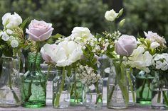 These yummy arrangements were for a pretty vintage themed garden wedding. Each table was crammed with little glass bottles and jars spilling with roses, tulips, sweet William and wild flowers.