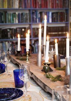 Joulupöytää koristaa kynttilöiden meri, joka on aseteltu lankun päälle. Kuva Kirsi-Marja Savola