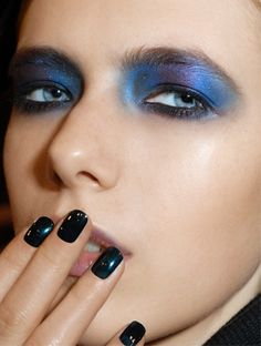Mix of middle sky blue and hint of violet,  black undereye shadow. Light blue eyes. Black nailpolish.