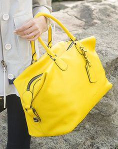 Perfect for summer travels and weekend adventures, the Coach Explorer Bag makes a statement in bright, bold yellow pebble leather.
