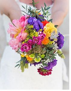 The bridesmaids will carry loose bouquets of coral peonies, purple stock flowers, pink wax flowers, yellow solidago, green geranium foliage, fuchsia spray roses, orange calendulas, yellow parrot tulips, jasmine vine, blue scabiosa, and jasmine vine wrapped in jute ribbon.