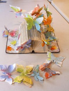 Book sculpture decorated with butterflies, hand watercolored and cut from book pages.  Butterflies are attached with wires. By Kendra Ferreira