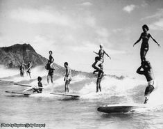 Surfers performing stunts in Hawaii, 1960s