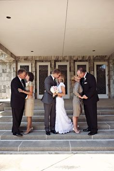 the bride and groom kissing, with both sets of parents kissing