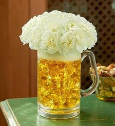 such a cute idea! white flowers in a beer mug filled with candy with golden wrappers!