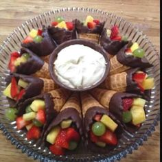 Use Ice cream cones, dip the top in chocolate, add fruit and add your favorite fruit dip to the middle!! So easy!!