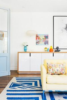 Dreamy home in Australia with mid-century Danish modern white and blonde wood sliding door credenza, colorful art and ceramic accents, a sunny yellow sofa, floral throw pillows, light blue painted French doors, and a bold blue and white cabana stripe area rug.
