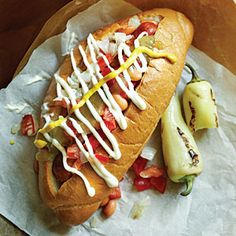 Sonoran Hot Dog - Bacon wrapped hot dog topped w/ pinto beans, grilled onions, tomatoes, jalapeno sauce, mayo, and mustard.