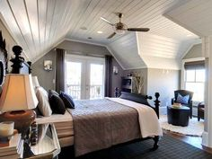 Attic Bedroom: white beadboard ceilings, double patio doors, natural light, ceiling fan, sitting area.