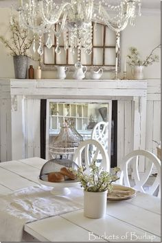 Vintage Country Farmhouse Style. Farmhouse dining room. Spring mantel with ironstone pitchers, pear blossoms, ink bottles and candles. Farm table. Walls are cotton fluff by BEHR. Chandelier. Buckets of Burlap home and blog