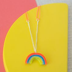 Acrylic Rainbow Sweet Thing Necklace: A cute necklace with an acrylic rainbow. A charming and magical necklace featuring a rainbow pendant crafted with colored and glittered acrylic and with a silver coloured chain. The necklace also comes with a metal plaque. These amazing necklaces make great gifts for teens, but we are finding women of all ages are buying them for themselves in our shop - they finish off a summer outfit perfectly! Packaged in a cardboard 'Sweet Thing' presentation box…