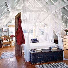 bed in the middle of the vaulted room with ceiling attached netting... a romantic nautical feel with navy, red, blue, white, wood