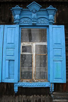 Window in an old Siberian wooden house in Ulan-Ude, Buryatiya, Russia. This shade of blue is traditional in the area.
