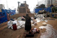 Una mujer defiende a un protestante herido de un bulldozer militar.  Egipto, 2013. - See more at: http://culturacolectiva.com/20-imagenes-que-nos-devuelven-la-fe-sobre-la-humanidad/#sthash.zgeBuaUN.dpuf