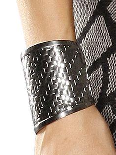 Armspange aus nickelfreiem Metall in Flecht-Optik. Offen, Breite ca. 5,3-7,5 cm, Durchmesser ca. 7 cm. Obermaterial: 100% Metall...