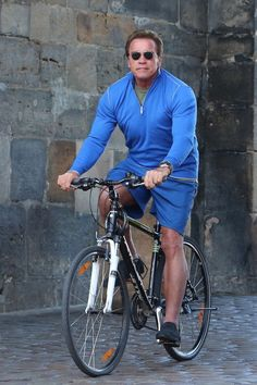 Arnold Schwarzenegger rides a bike in Prague