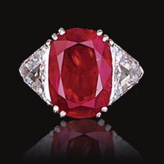 ATTRACTIVE RUBY AND DIAMOND RING Claw-set with a cushion-shaped ruby weighing 6.11 carats, between triangular diamond shoulders, mounted in platinum.