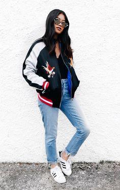 Street style look com body preto, calça jeans, tenis adidas e bomber jacket.