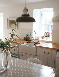 butcher block countertops, industrial pendant lights, deep-set porcelain sinks. Via The Design Sponge.