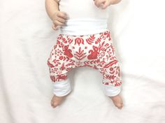 READY TO SHIP!  Perfect for your stylish winter babe, these soft grow-with-me leggings feature a mod Scandinavian Folkart print in red and cream, with white cuffs! A bum patch allows extra room for baby to move in, whether theyre in cloth diapers or disposables, and the wide stretchy waist band ensures these pants stay up! Also GREAT for babywearing - adjustable cuffs mean no bare ankles in chilly weather.  SIZING :: Recommended for ages Newborn - 6 months, or 5-15 pounds. This fit is…