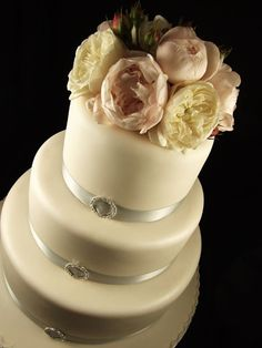 Three-tiered wedding cake trimmed with silver ribbon and peonies