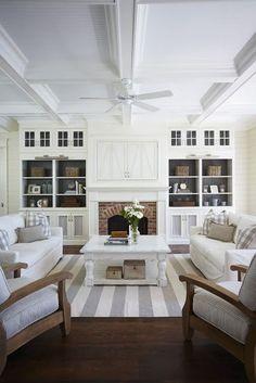 Built-ins with darker paint color behind, tv hidden behind doors above fireplace.