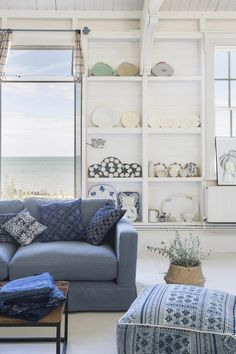 Dreamy! A white sitting room with a blue sofa, lots of throw pillows and white shelf racks with beautiful pottery in the background. Image by DFS Furniture.