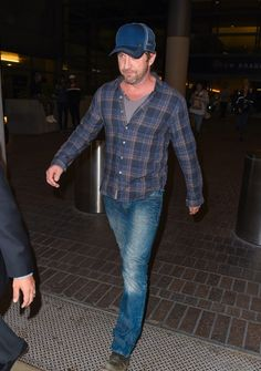 Gerard Butler in Blue Jeans. He wore a pair of straight cut, very fitting blue jeans in a medium wash, paired with a plaid flannel shirt layered over