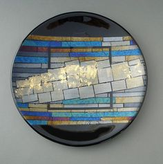 Formations by Sabine Snykers. This kiln-formed platter is composed of iridescent and black elements. Gold leaf is permanently fired onto the glass. Signed on back. Platter comes with a clear acrylic stand that can be wall mounted with two screws or stand alone.