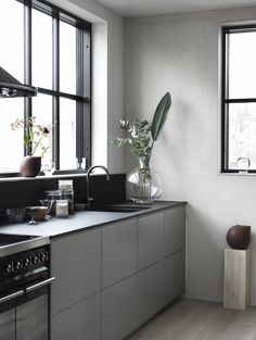 Minimal and industrial kitchen - The black and grey fronts and worktop match perfectly with the concrete walls and the large black frame windows.