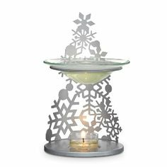 Pierced metal snowflakes fall into line for a fashionable winter display. Place a tealight in the base to release the fragrance from Scent P...