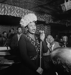 Ella Fitzgerald, Dizzy Gillespie swooning on her right and Ray Brown on bass behind her.
